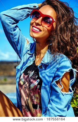 fashion stylish beautiful young smiling brunette woman model in summer hipster bright colorful casual blue clothes posing in the street