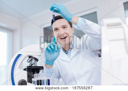 Keep an eye. Handsome scientist keeping his mouth opened looking upwards while checking chemical agent