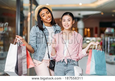 portrait of stylish women friends shopping together at shopping mall