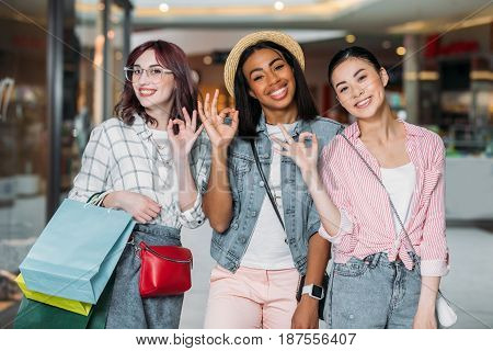 Portrait Of Smiling Women With Shopping Bags Showing Ok Signs At Shopping Mall