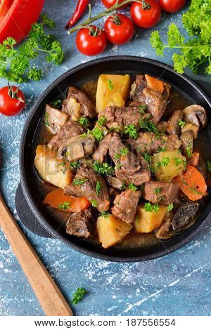 Meat goulash with vegetables potatoes and mushrooms on concrete grunge background