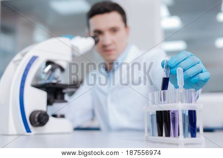 Choosing necessary one. Attentive scientist sitting at his workplace and looking at his hand while taking special glass with chemical reagent