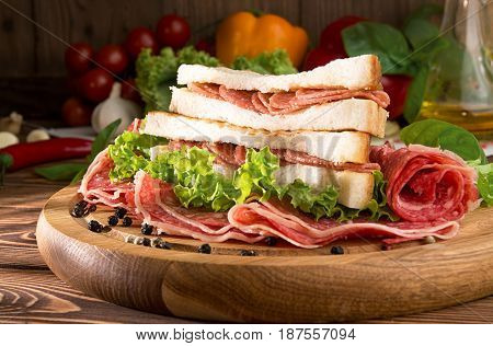 Sandwich With Salami. Lettuce, Cherry Tomatoes, Mustard, Basil, Garlic On Wooden Background.