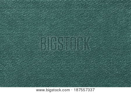 Dark green background of soft fleecy cloth. Texture of light dark cyan nappy textile closeup.