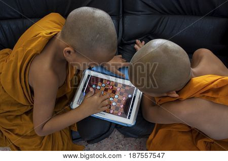 BANGKOK THAILAND - JANUARY 9 : two little buddha monk playing draughts game in computer tablet at temple on january 9 2013 in bangkok thailand