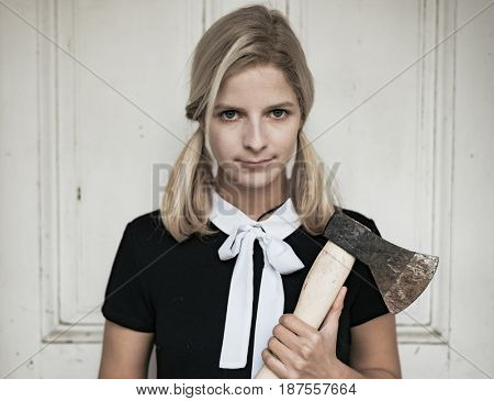 Creepy blonde woman in halloween costume with an axe