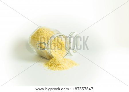 Dry And Raw Rice Falling Out Of A Laid Glass Jar Isolated On White Background