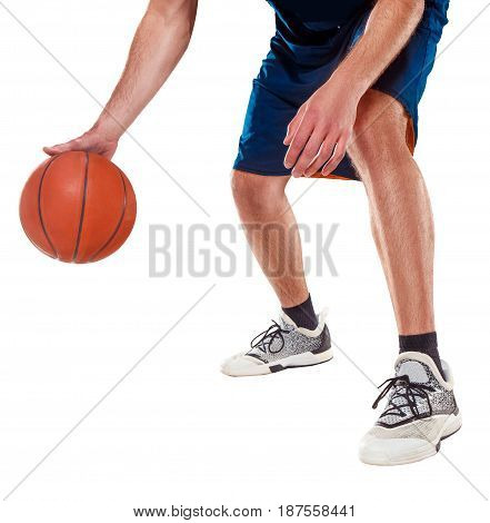 The feet of a basketball player with a ball against white studio background