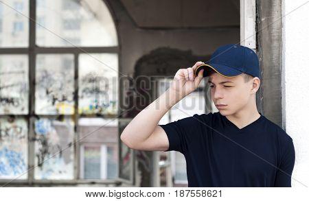 young man stands near an old broken window