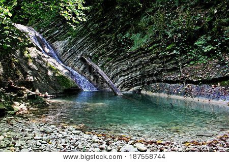 A small picturesque waterfall in the mountains of the North Caucasus.