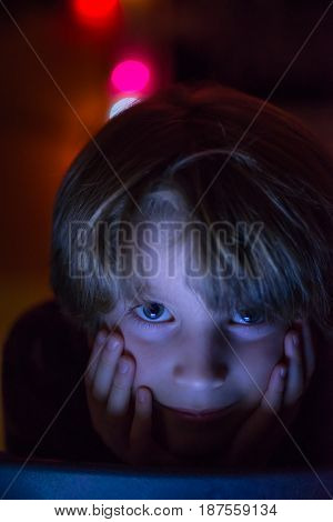 Young boy looking at tablet at night lit by the light from the screen