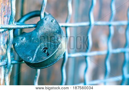 Old metal padlock hanging on the grate