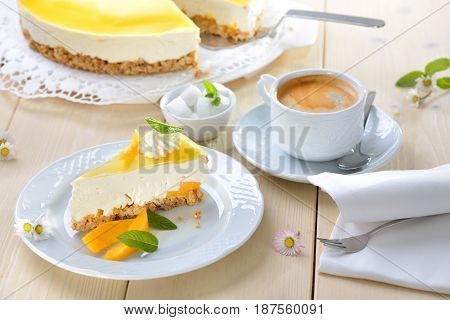 Fresh cheesecake with mango fruit and glaze, the flan case made of cookie crumbs, served with a cup of coffee