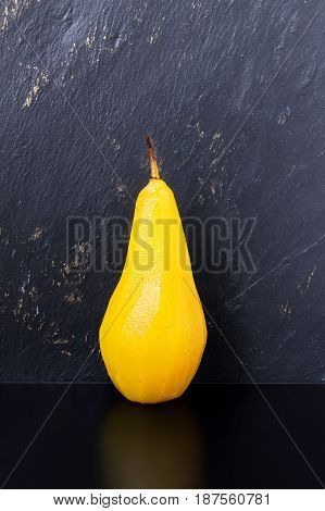 Single pear poached in sugar and saffron syrup on a black table with dark textured slate background