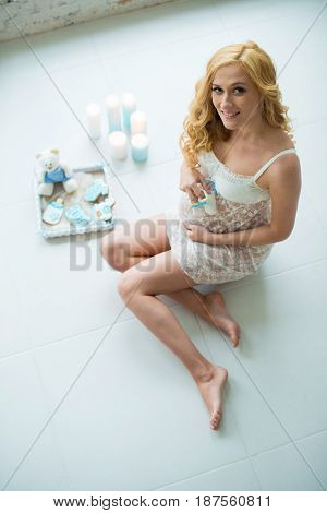 Beautiful pregnant girl sitting by the window with baby slippers