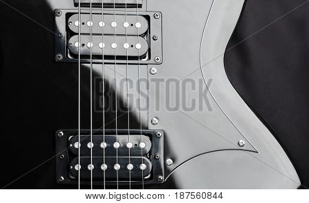 A fragment of a black guitar with steel strings. Dark background.