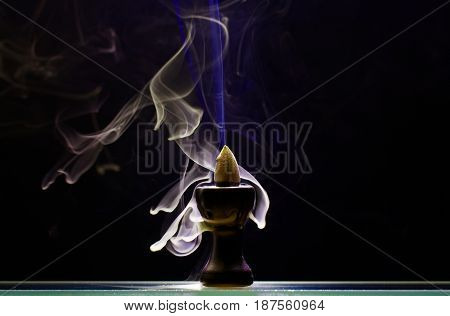 Aromatic cone smoldering in a ceramic stand on black background