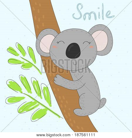 Grey koala bear on wood branch with green leaves.