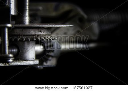 Geared to Type: A gearing mechanism from a classic 1940's typewriter with bokeh to faded black background. Suitable for business and industry advertising applications or as a wall decoration in business offices and hotel rooms that cater to the business c