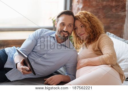Love, peace and harmony. Wife and husband watching a romantic film on a digital tablet together while relaxing on a bed.