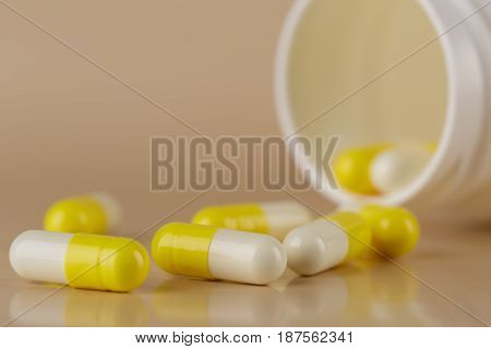 Heap of yellow capsules closeup on beige background
