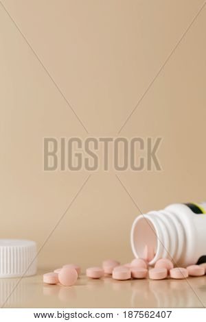 Round brown pills and white plastic bottle on beige background