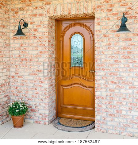 entrance of a home - stylish wooden front door in a detached house - embedded in a brick wall