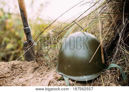 Metal Helmet And Sapper Shovel Of Infantry Soldier Of Soviet Russian Red Army During World War II, Lying On Sand In Trench.  Soldiers Military Ammunition Of World War II On Ground