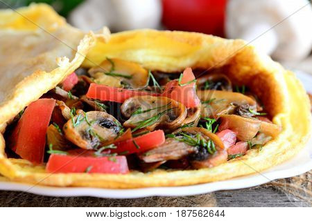 Yummy omelette with mushrooms and tomatoes. Fried omelette with mushrooms, fresh tomatoes and dill on a plate. Healthy vegetarian egg breakfast. Rustic style. Closeup