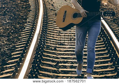 Walk on tracks with guitar. Women with guitar on the railway.