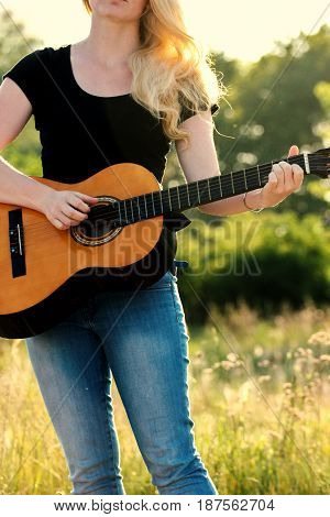 Play on the guitar in sunset. Women is playing on the guitar in nature.