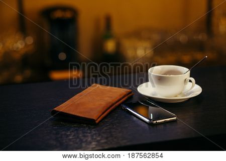 Tip on a restaurant tThe account on a bar counter, nearby phone and coffeeable