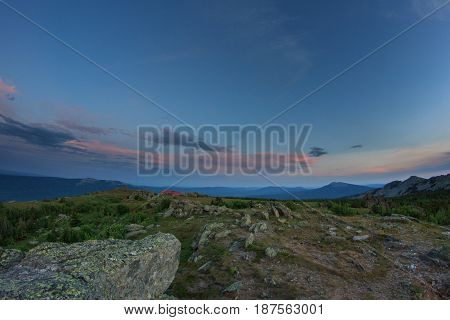 Sunset over the mountainous terrain. The nature of the Southern Urals. Sunset sky over the forest and the mountains. Panoramic view