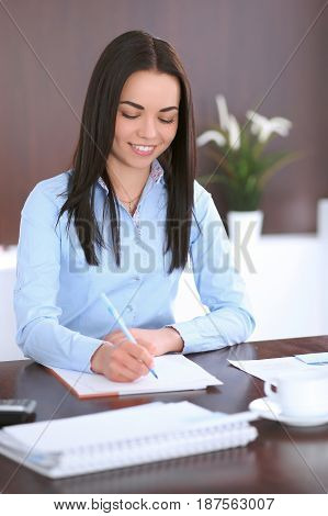 Young business woman sitting and writing at the table in office.