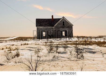 horizontal image of an old abandoned house with dead grass and snow all around with the sun starting to set in the early evening.
