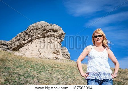 horizontal image of the top half torso of a caucasian female model  with reddish blonde hair posing in front of a large rock cliff in the summer