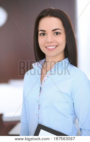 Young business woman standing in office. Success and education concept