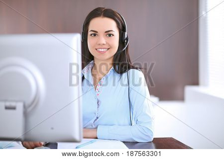 Young business woman in a headset, sitting at the table in the office.