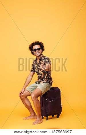 Image of smiling young handsome african man wearing sunglasses sitting on suitcase and pointing. Looking at camera.
