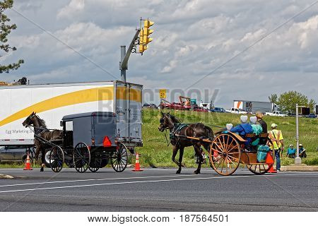 LANCASTER PA - MAY 14 2017: An Amish cart and carriage pass by the Make-A-Wish Foundation truck convoy. On the Mother's Day annual fundraiser truckers grant a Lancaster County wish ride to children with life-threatening illnesses.