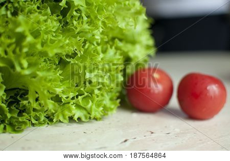 Bunch Of Raw Organic Green Frisee Salad And Two Tomatoes