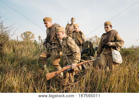 Dyatlovichi, Belarus - October 2, 2016: Reenactors Dressed As Russian Soviet Red Army Soldiers Of World War II Walking With With Maxim's Machine Gun Weapon In Autumn Meadow