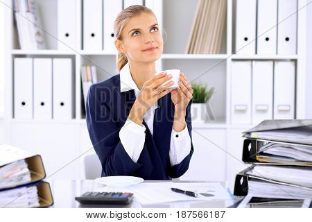 Happy business woman or female accountant having some minutes for coffee and pleasure at working place.