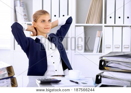 Happy business woman or female accountant having some minutes for time off and pleasure at working place.