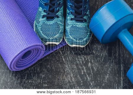 Yoga Mat, Sport Shoes, Dumbbells And Bottle Of Water On Blue Background. Concept Healthy Lifestyle,