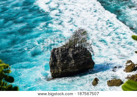 rocky island with tree in the middle foamy waves. Uluwatu Bali