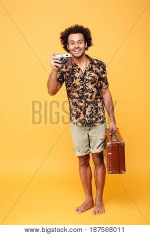 Full length portrait of a smiling african man tourist holding suitcase and taking a photo with retro camera isolated over yellow background