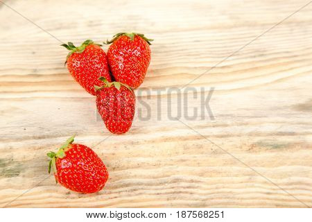 Juicy strawberries on a light wooden background