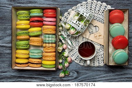 Macaroons in the box with decorations and a cup of tea