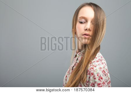 Young beautiful blond girl in blouse with a pattern of flowers. Long blonde straight hair.
